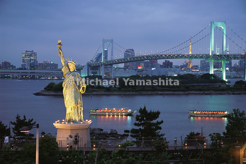 Japan's infatuation with Americana rises to obvious extremes near Odaiba, where a Statue of Liberty replica stands tall before the Rainbow Bridge - so named for its changing colored lights. Tokyo Bay, Japan.