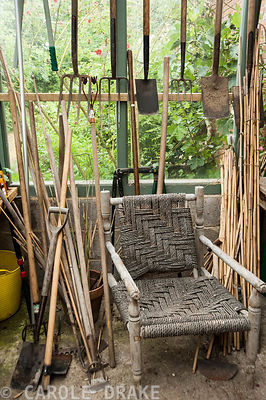 Gardener's chair surrounded by tooks in the glasshouse. Private Garden, Wiltshire, UK