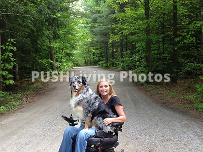 Young woman using a power wheelchair on a forest road with her dog