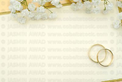 Wedding rings with flowers on blank card Copy space