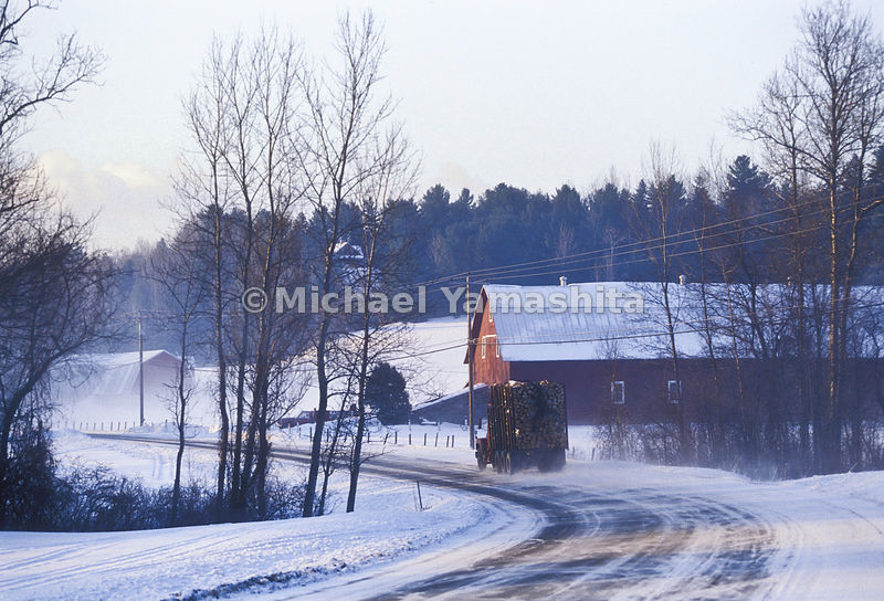 A Logging Truck Moves Down A Wintery Vermont Road.