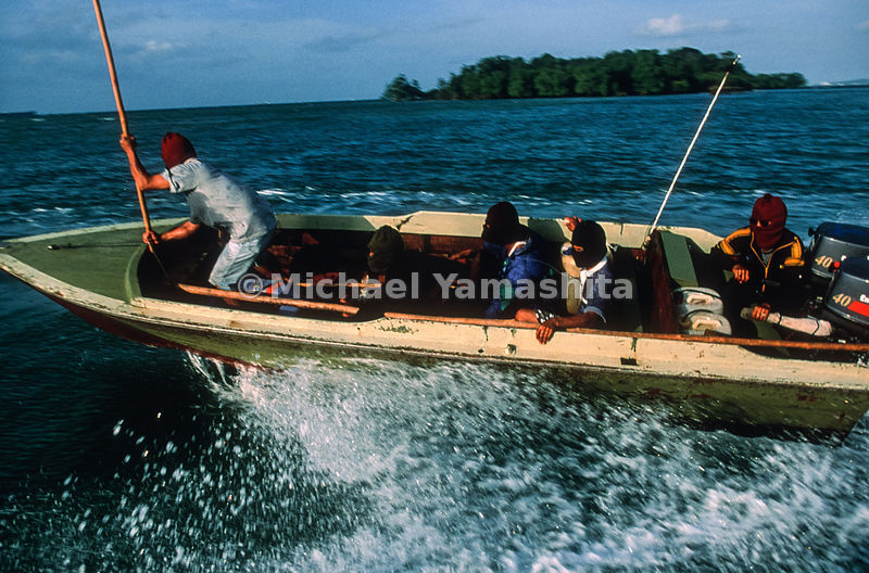 When darkness falls, pirates will zoom close on a speedboat, board over the stern, and, armed with knives, rob the crews of ships.  Riau Islands, Indonesia.