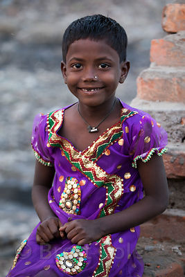 A girl smiles for a portrait near the Dhapa landfill, Kolkata, India. Hundreds of people work at farms and recycling facilities near the landfill.