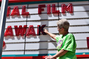 A woman places letters on a movie theater maquee