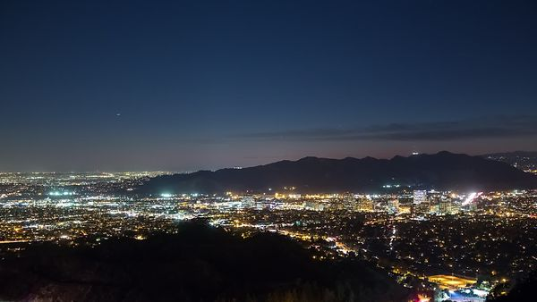 Bird's Eye: Panning Small Mountains Silhouetted By City Lights