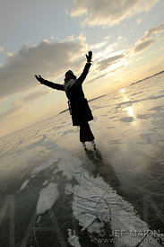 Young woman with raised arms ice skating on frozen sea