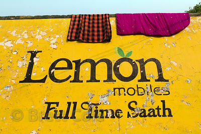 Advertisement and laundry on a wall in Aaram Baagh, Rajasthan, India