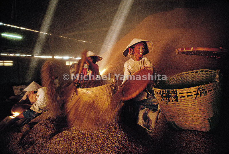 "At a rice mill in Soc Trang, the heart of Vietnam's ""rice basket,"" women collect bran to sell as animal feed. The factory allows villagers, who allso use the husks for cooking fires, to haul these waste products away for free."