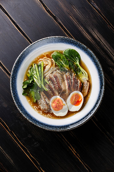 Ramen noodles with Duck, egg and pak choi cabbage in bowl on wooden background