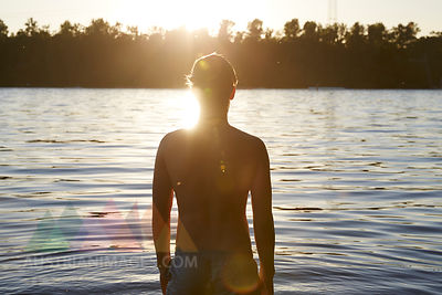 Back view of man in a lake at sunset