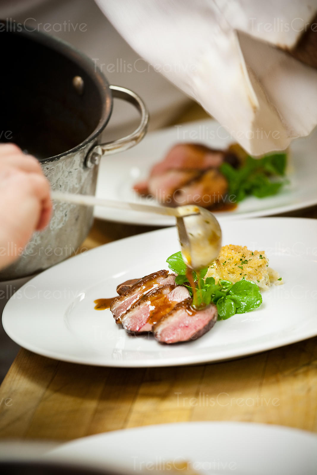 A chef pours au jus over a plate of meat in a busy restaurant kitchen