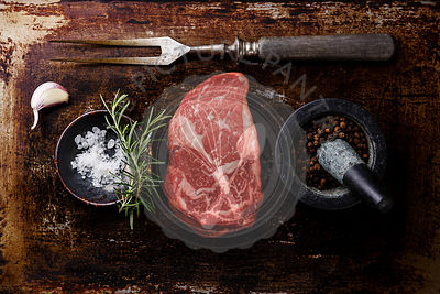 Raw fresh marbled meat Steak Rib eye Black Angus, seasoning and fork on dark metal background