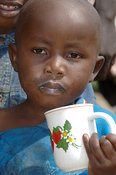Young African boy drinking milk some around mouth Kenya Africa