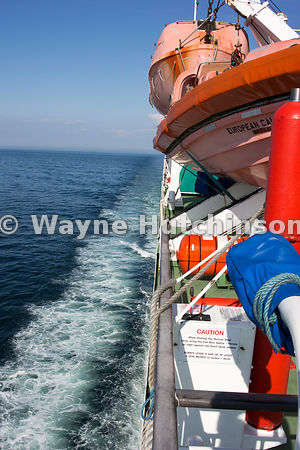 Lifeboats and sea wake on a ferry from Cairnryan to Larne, on a still day. UK