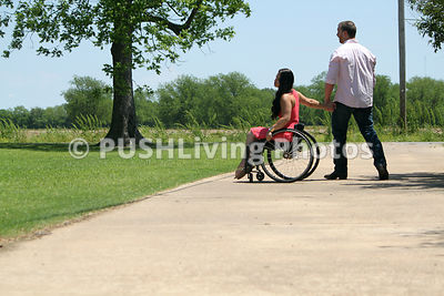 Young woman in a wheelchair in a park with her boyfriend