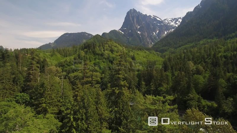 Side aerial reveal of cascading river and mountains with green forest all around. Index Washington State