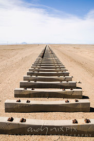 Rusted railway tracks ending, with empty concrete railway sleepers in the foreground, tracks disapearing into the desert in the distance