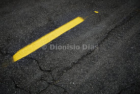 Yellow strip on asphalt street worn out.