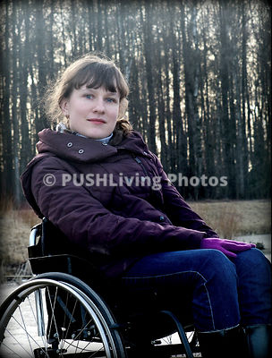 Young woman in a wheelchair in a forest