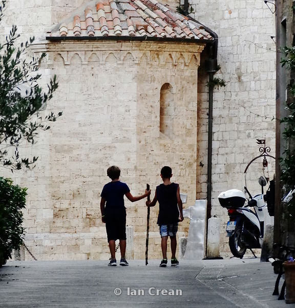 Two boys walking in a quiet side street of San Gimignano
