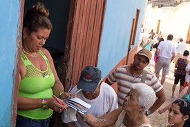A woman checking people's ration books to distribute food in Trinidad, Cuba.