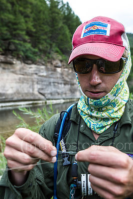 Fisherman David Allen tying a new fly on his line.