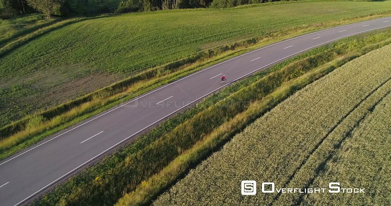 Man biking on the countryside, C4K aerial descending tilt view towards a biker driving on a road, between wheat fields, on a sunny summer evening sunset, in Uusimaa, Finland