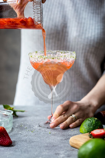 A woman is photographed as she is pouring margarita into a margarita glass full of crushed ice.