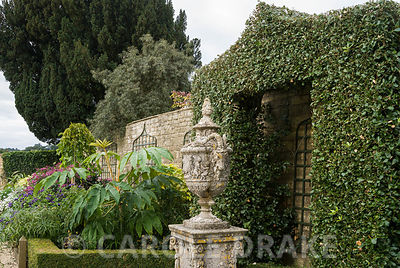 Shrub clipped into shape like a pointed arch frames a classical urn in the White Garden. Bourton House, Bourton-on-the-Hill, Moreton-in-Marsh, Glos, UK