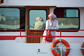 A woman standing on a deck of a ferry in Istanbul.