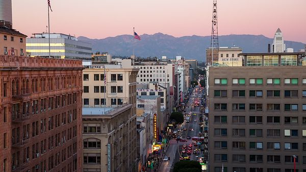 Bird's Eye: Mid-Rises & A Busy Broadway Ave. Lights Up Amidst A Backdrop of Mountains (Day to Night)