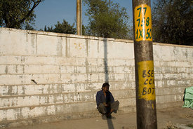 India - Delhi - A homeless mentally ill man sits alone by the side of the road