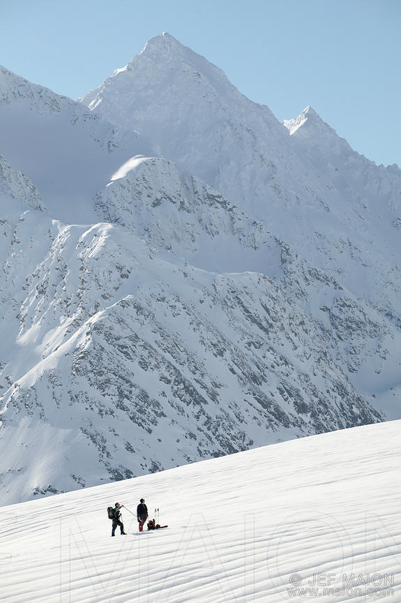 Skiers below snowcapped mountains