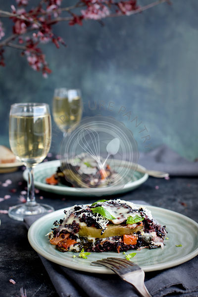 Black Rice Eggplant Parmesan sreved with white wine and bread.  Photographed on a black/greay background.