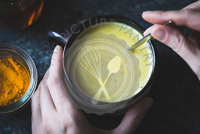 Hands holding golden milk - Mixed honey, turmeric, ginger, cardamom, and cinnamon