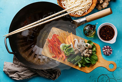 Cooking process Udon noodles with oyster mushrooms and vegetables in wok pan on blue background