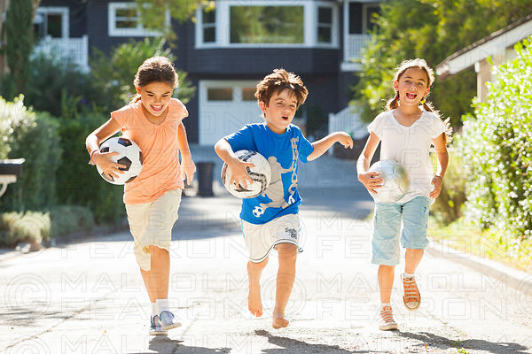 three children running holding soccer footballs in a suburban street