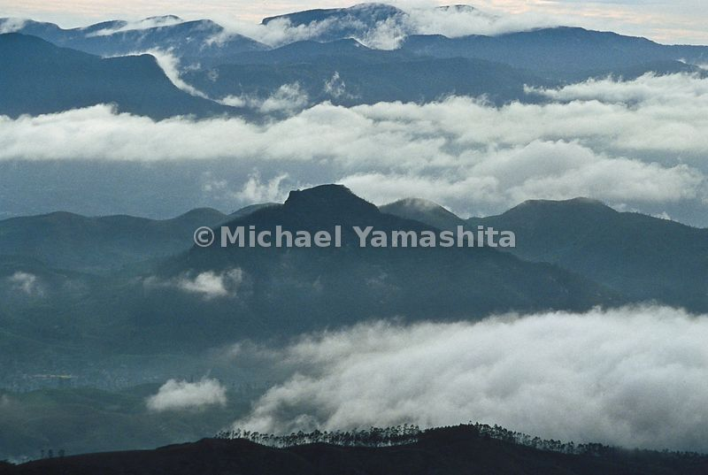 Mountains throw off blankets of clouds at dawn in a view from Adam's Peak.