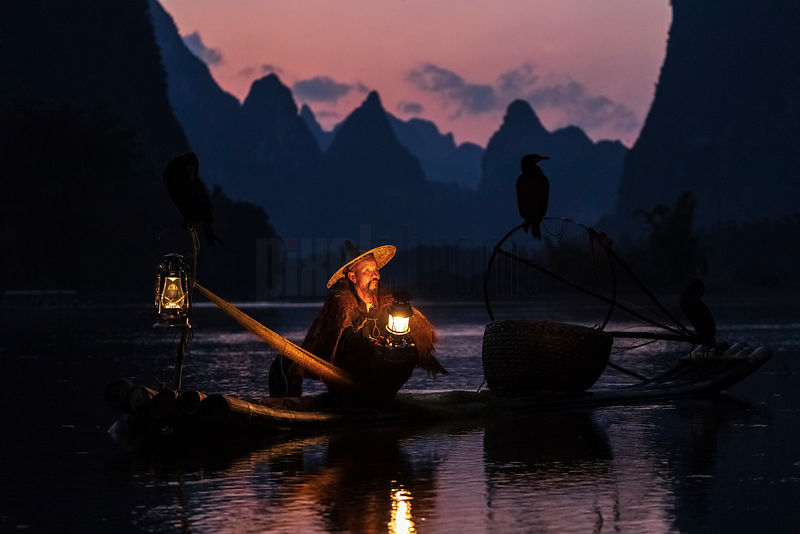 Traditional Cormorant Fishermen in the Li River at Dusk