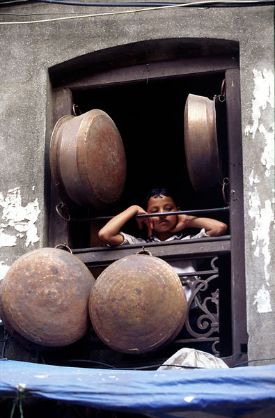 A girl stares out of a window surrounded by cooking pots, Kathmandu, Nepal