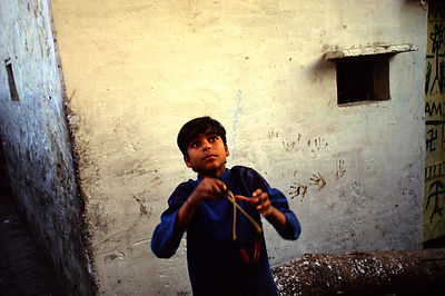 India - New Delhi - A boy shoots his catapult at birds