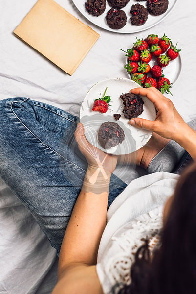 A woman with jeans sitting and eating cookies and fresh strawberries. An old book, a plate of fresh strawberries and cookies accompany.