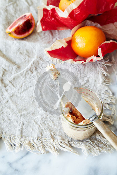 Whipped blood orange butter in jar with knife