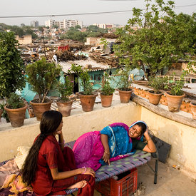 Radhika and her neighbour Saroj on her roof garden in one of Delhi's largest slum's Kesumpur Pahari. The slum, built more than thirty years ago has no running water or sewage facilities but many have beautified their homes with plants and flowers