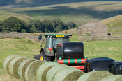 Wrapping big bales of silage with plastic film, Swaledale, North Yorkshire, UK.