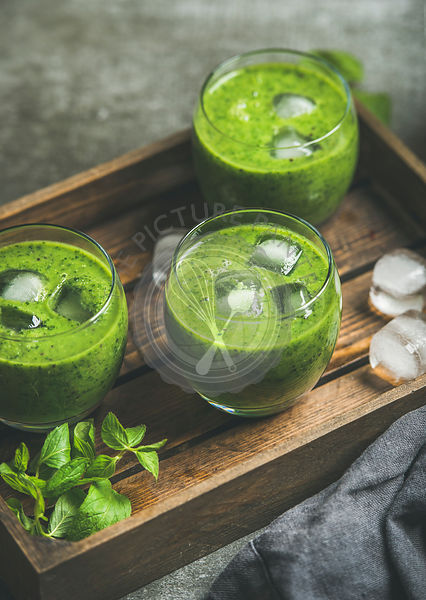 Fresh green smoothie in glasses with ice cubes, mint and lime in wooden tray over grey concrete background