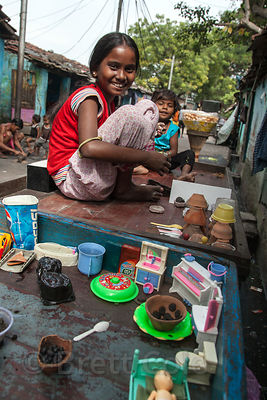 Children play on a wooden cart in the Fakir Bagan area of Howrah, India. They've made small representations of roti flatbread and sweets in the bowls.