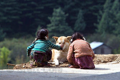 Two sisters pet a stray dog in Manali, India