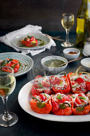 Black Rice Caprese Stuffed Roasted Red Peppers served with a fresh Basil Oil and white wine.  Photographed from front view on a dark blue background.