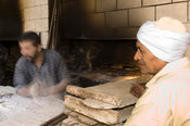 man baking traditional flat bread, Alexandria, Egypt